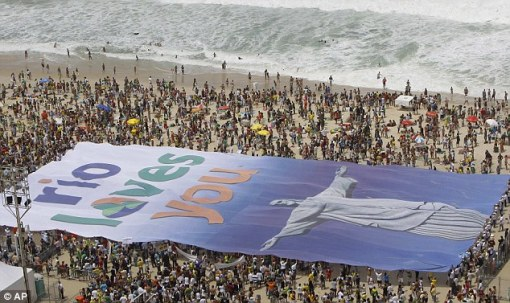 Rio de Janeirans hold up this huge banner with an image of Christ the Redeemer as they gather on Copacabana beach in Rio while they wait for the IOC's announcement